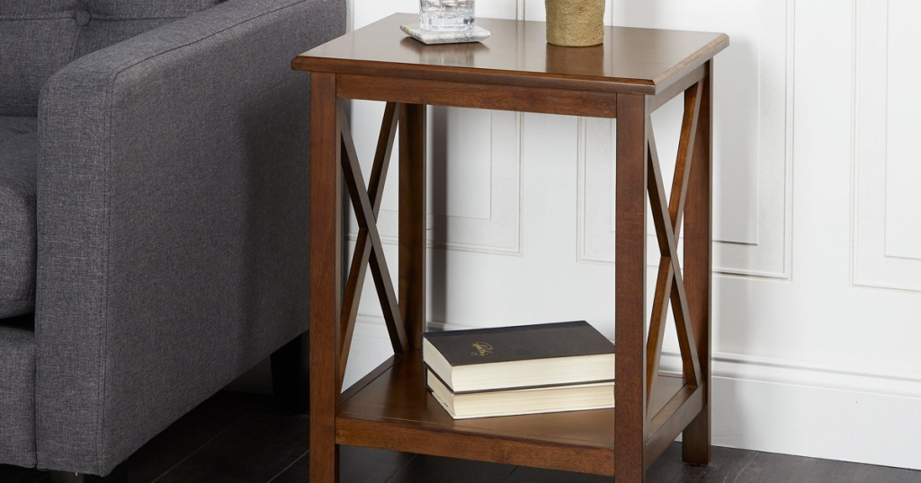wood side table in cherry finish with wooden x's on each side and books on the lower shelf