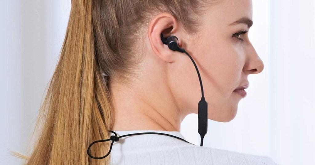 aukey wireless headphones in womans ears