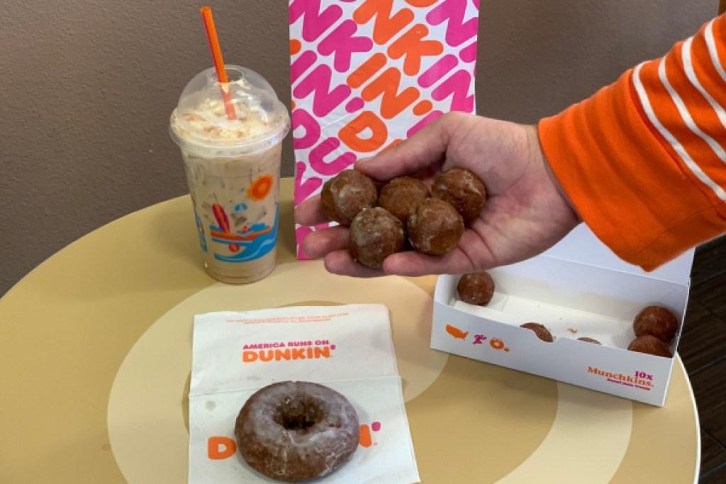 dunkin donuts hand holding munchkins