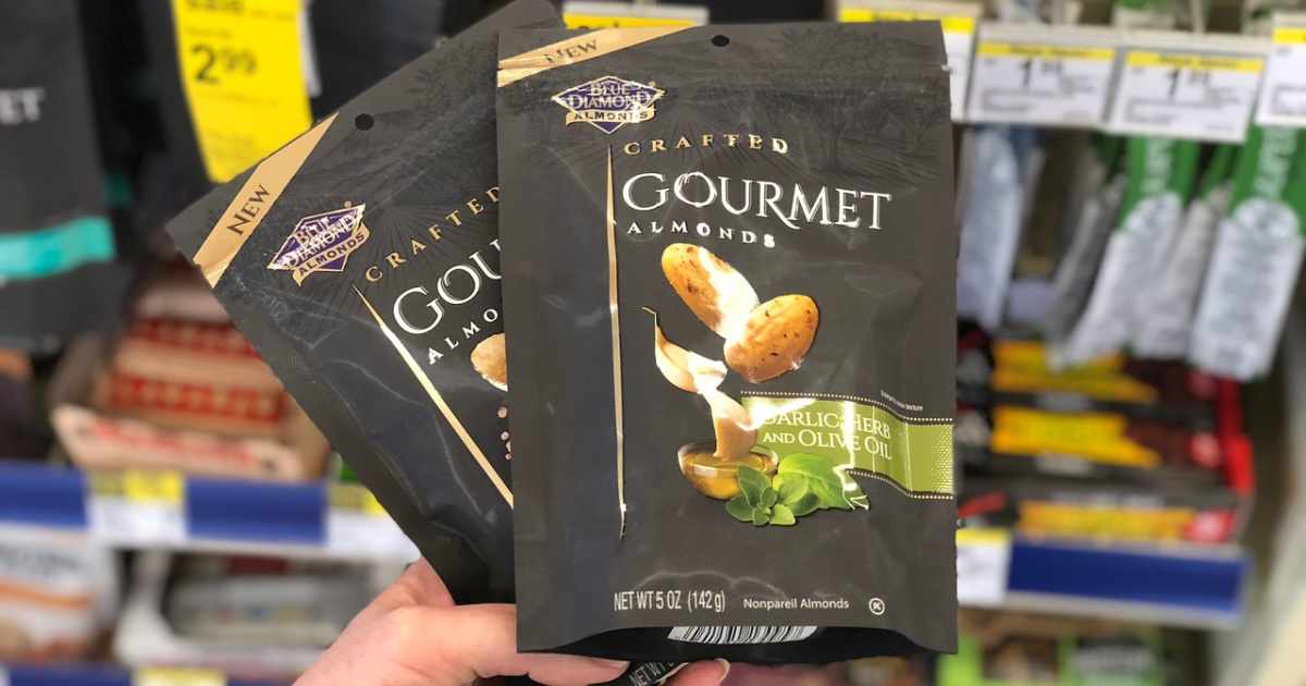 hand holding 2 bags of Blue Diamond Gourmet Almonds in a store