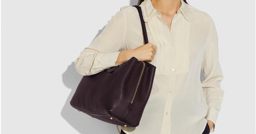 woman wearing white blouse carrying black handbag