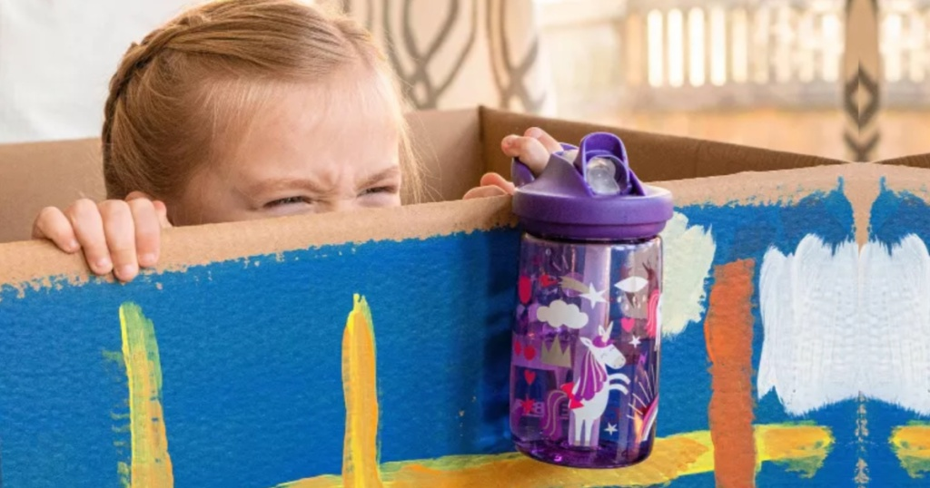 little girl peeking out from inside a box holding a water bottle with unicorns on it