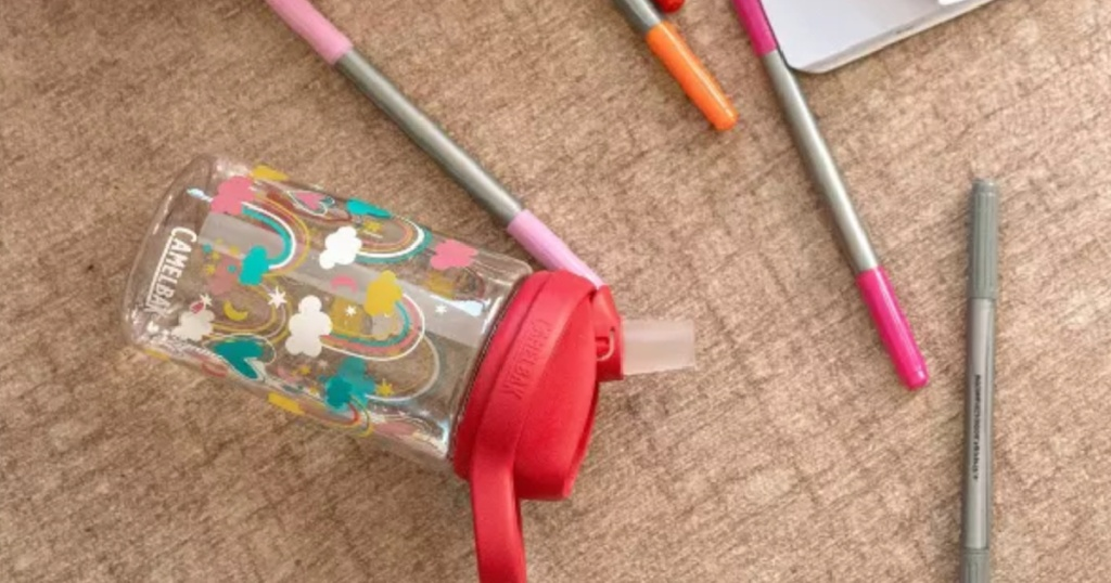 kids clear water bottle with rainbow laying sideways on the floor next to coloring markers