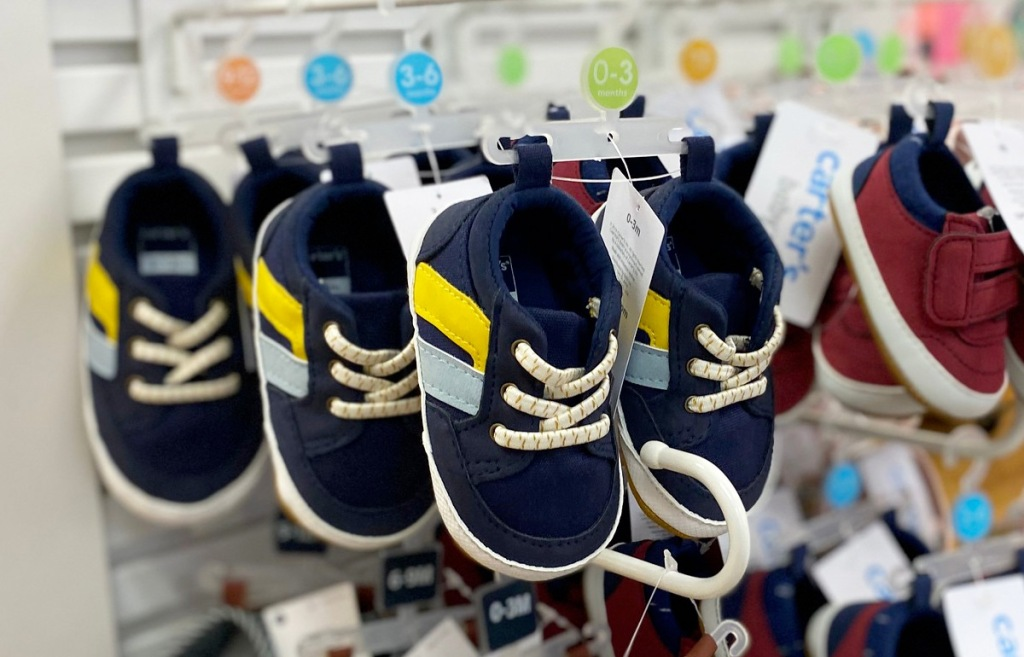 navy blue baby boy sneakers with yellow and light blue stripes on Carter's store display racks