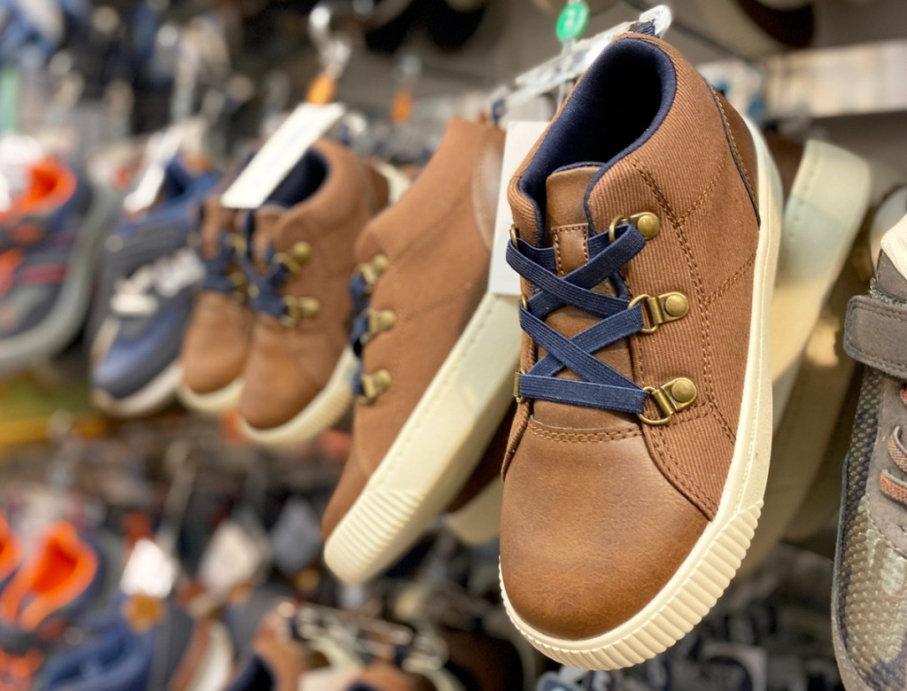 brown leather toddler boy high top sneakers with blue laces hanging on Carter's store display racks