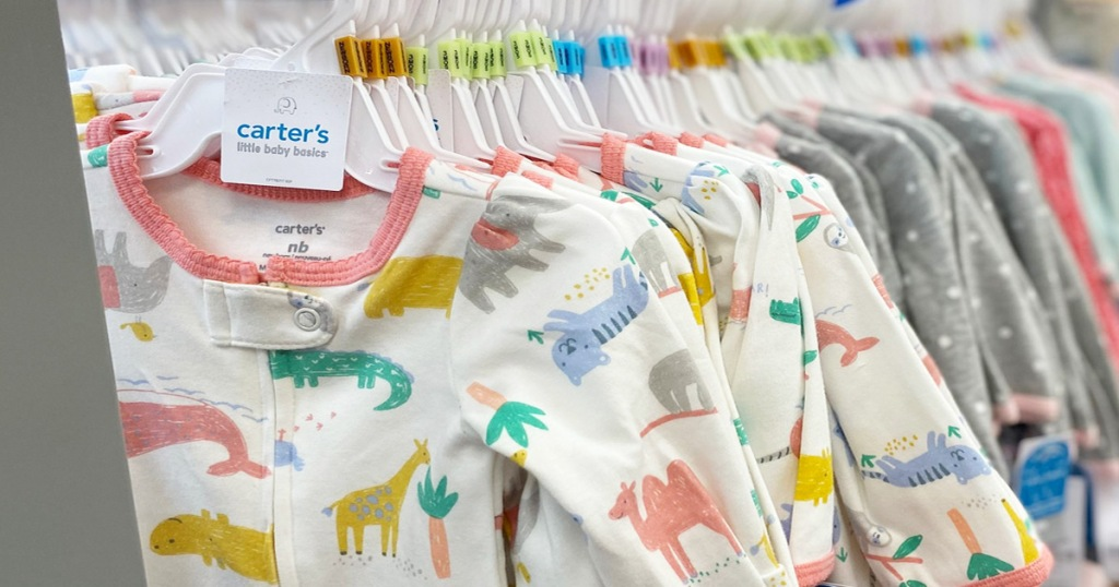 carter's baby girls pajamas on hangers hanging on store display rack