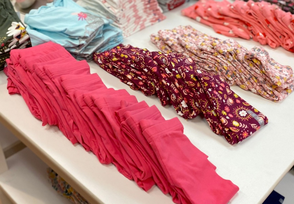white display table full of folded girls leggings in various pink and printed patterns
