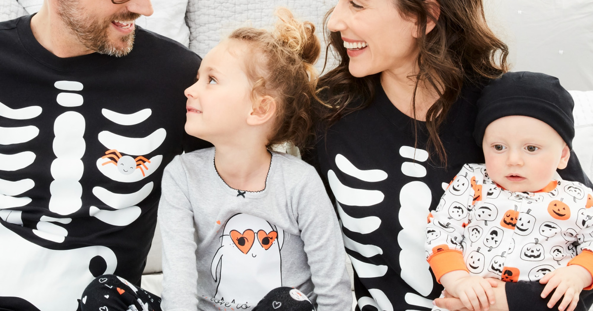 family sitting wearing carter's spooky matching pajamas