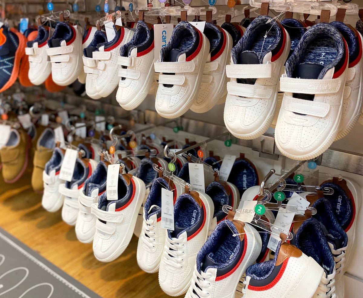 pairs of white toddler boys sneakers on hangers on Carter's store display