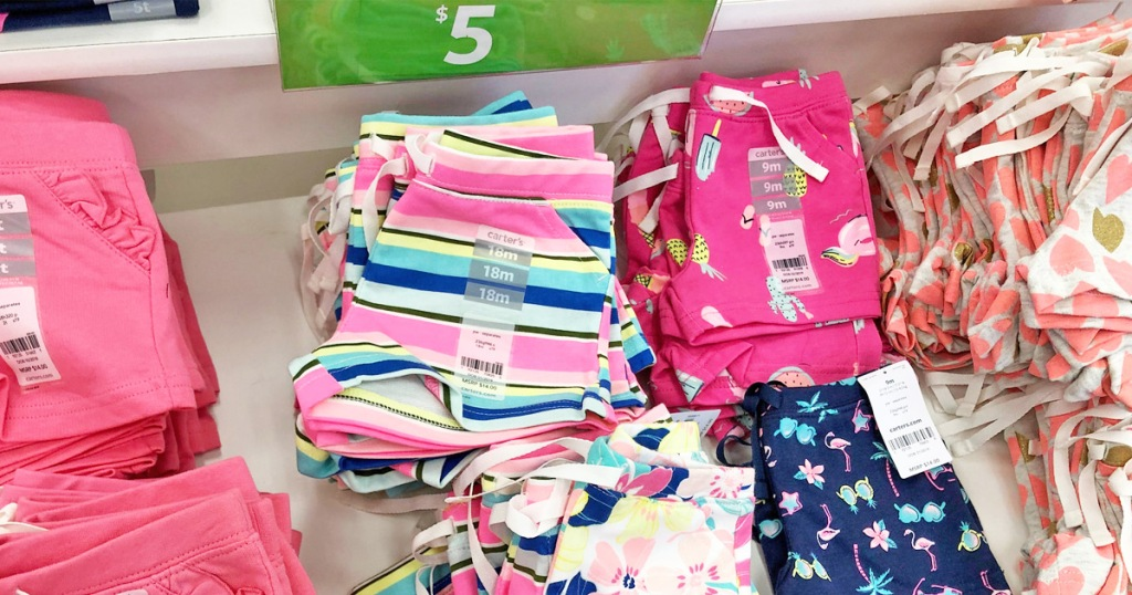 folded Carter's toddler girls shorts on store display table