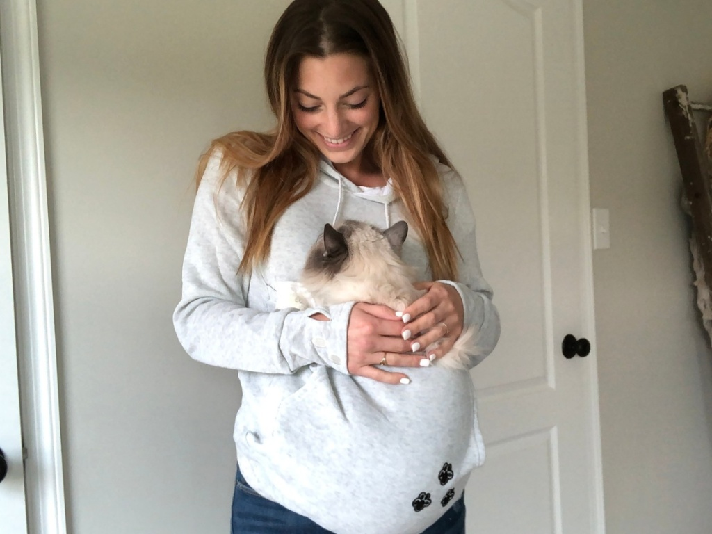 woman wearing a grey hoodie with a cat sitting in the pouch