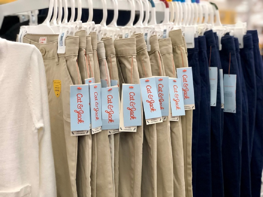 various colored kids uniform pants hanging on rack in store