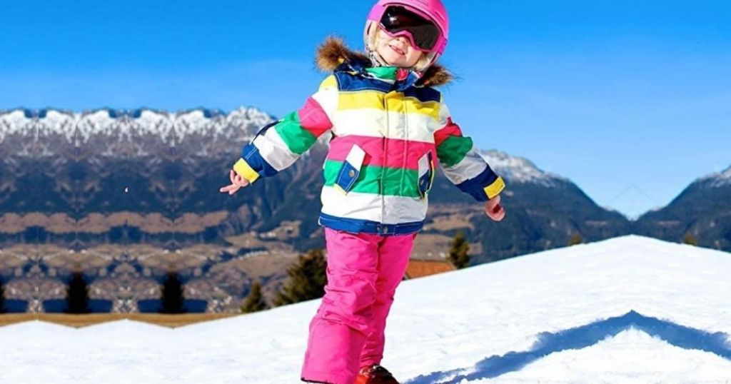 little girl wearing a snowsuit out in the snow