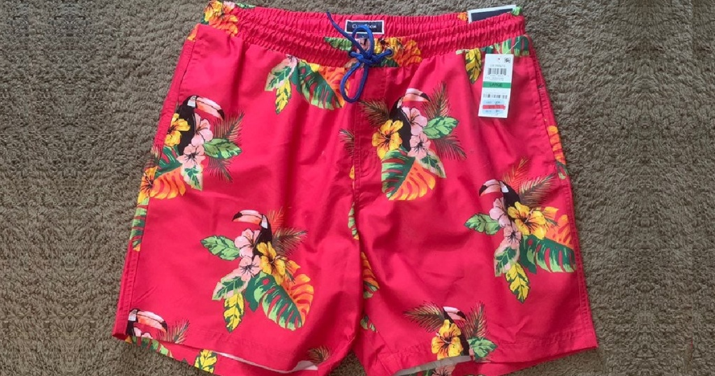 men's pink tropical print swim trunks on carpet