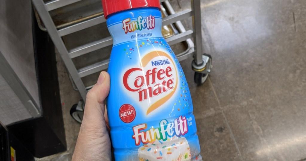 Hand holding Funfetti Coffee-Mate Creamer in store