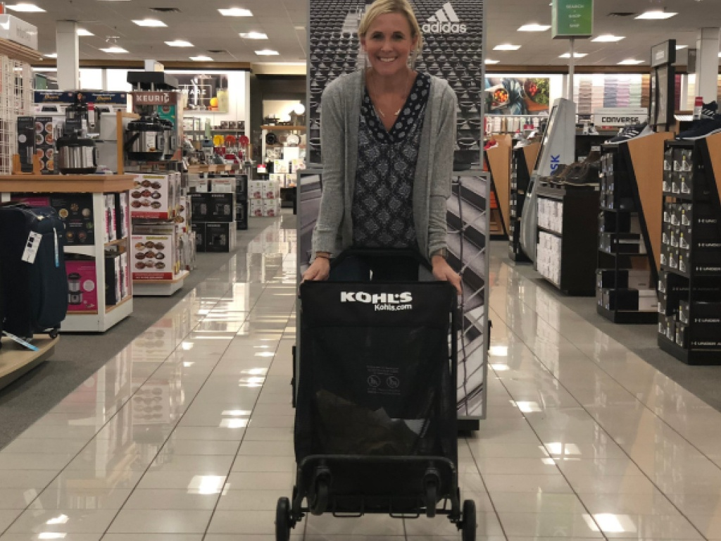 woman leaning on black shopping cart in store
