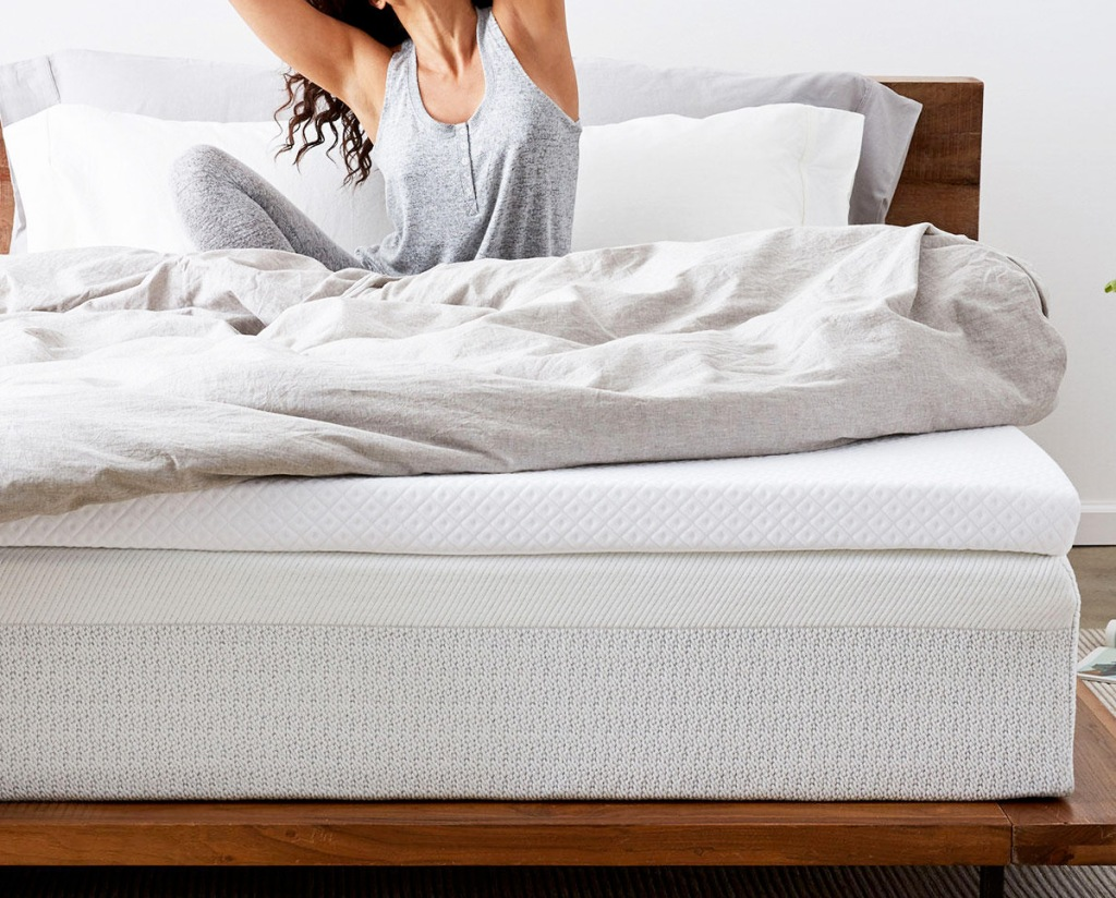 person sitting on bed with grey comforter and white mattress topper on top of mattress