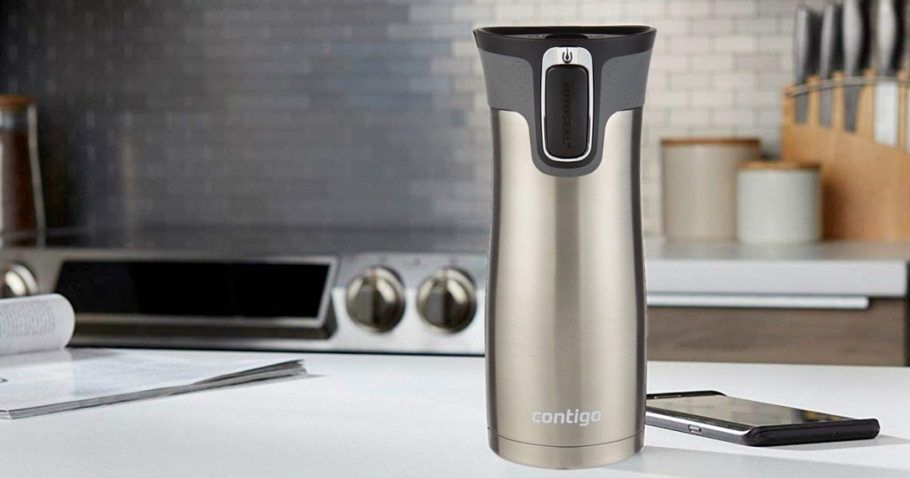stainless steel travel mug with black lid sitting on a kitchen counter