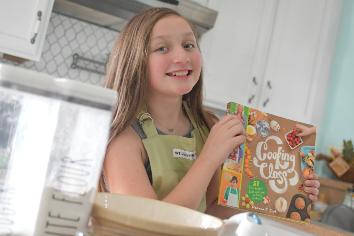 Girl holding Cooking Class Cookbook