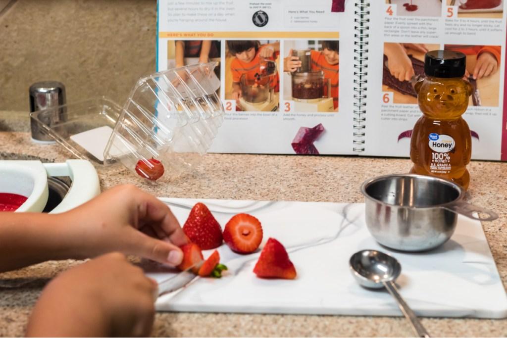 Boy cutting up strawberries