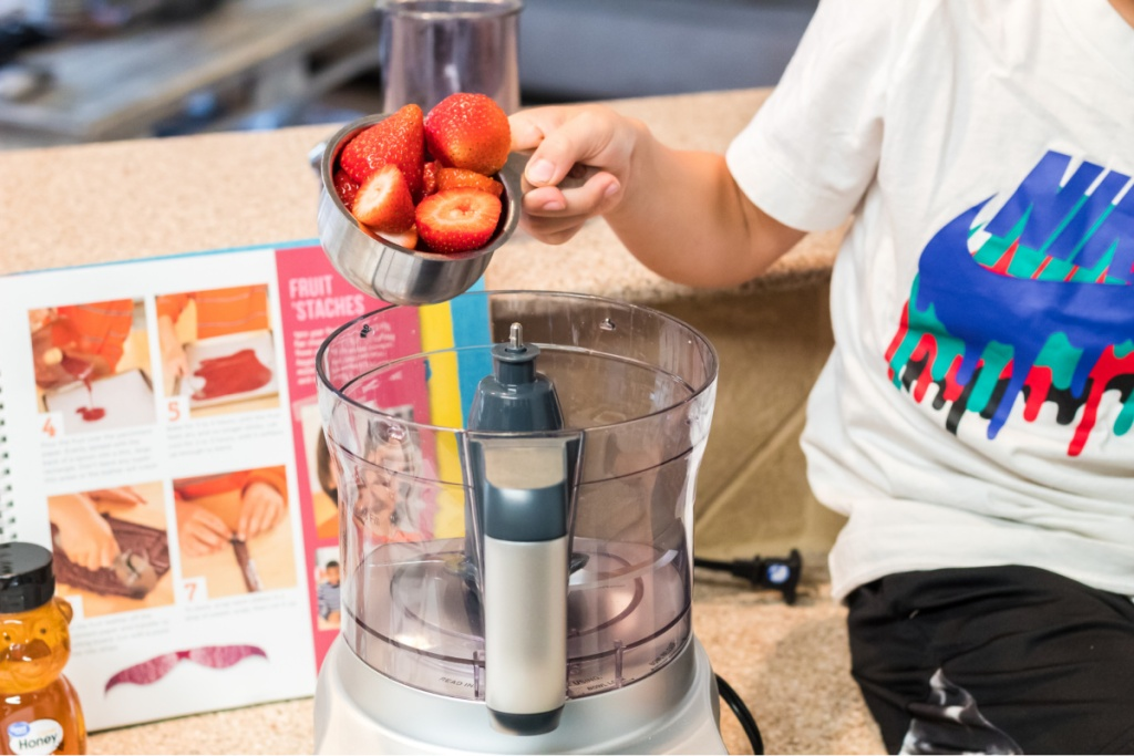 boy pouring strawberries into a food processor