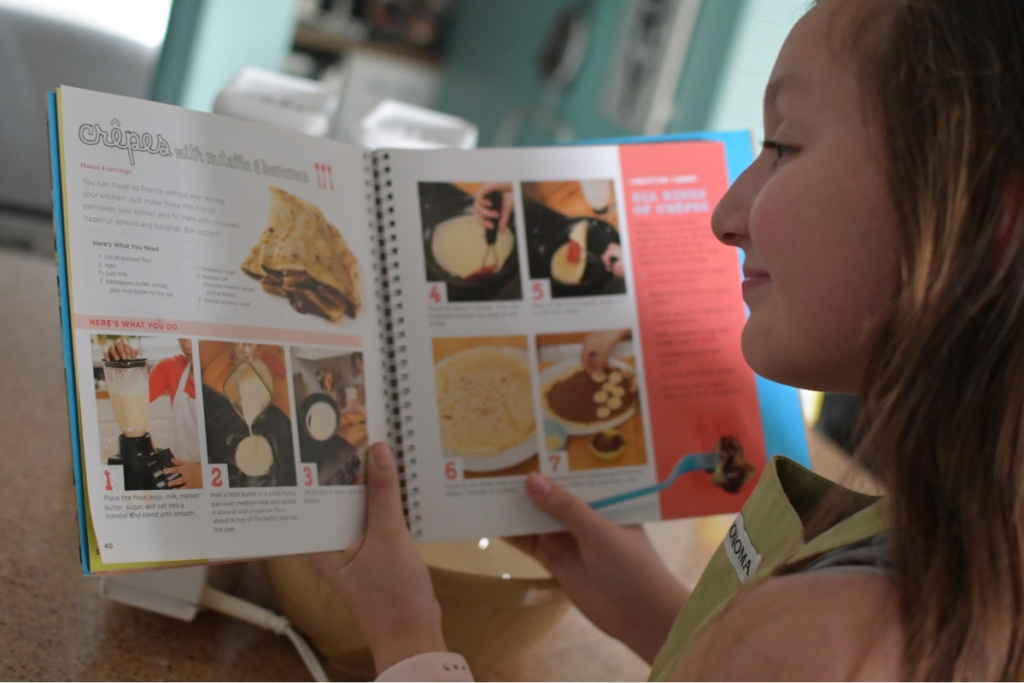 Girl looking over directions for Cooking Class Recipe