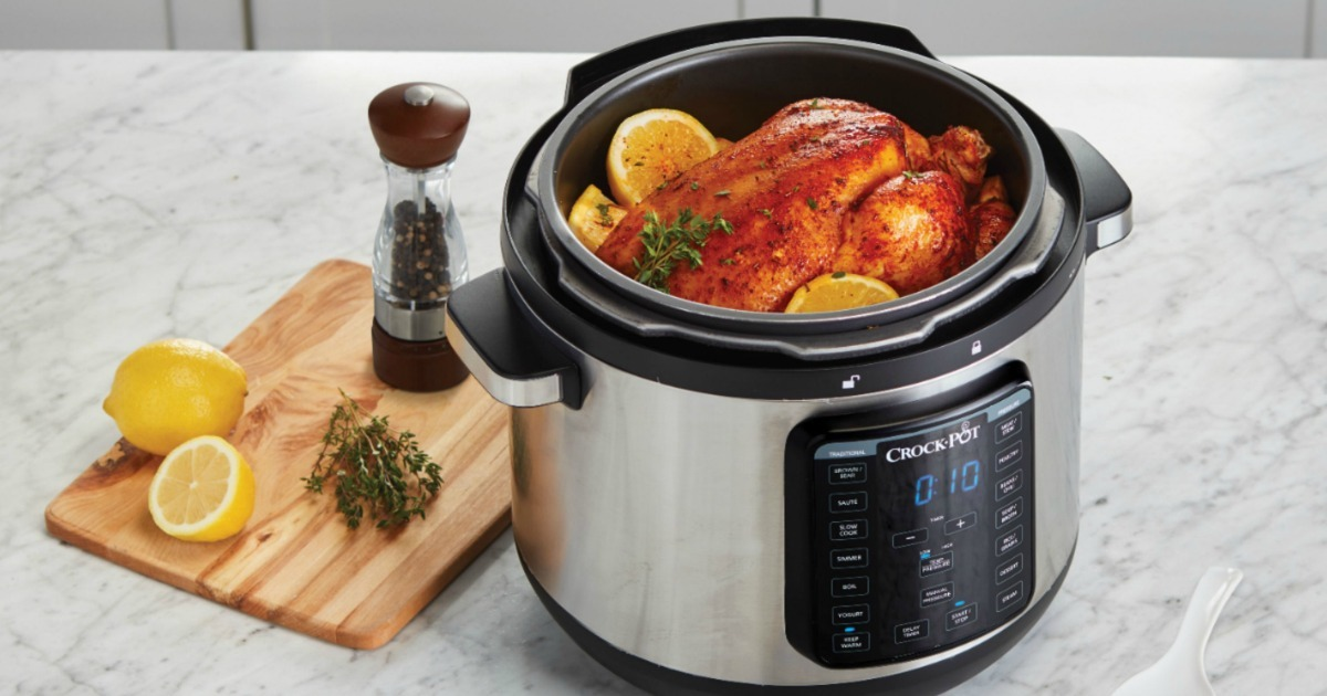 Large pressure cooker on counter with chicken and lemons inside, near wooden cutting board