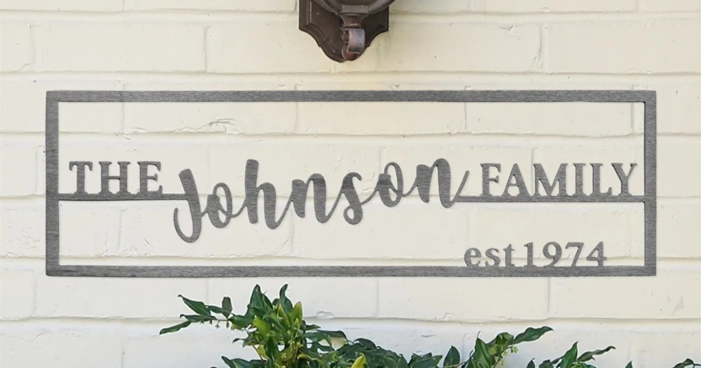 family name plaque on outdoor wall with foliage