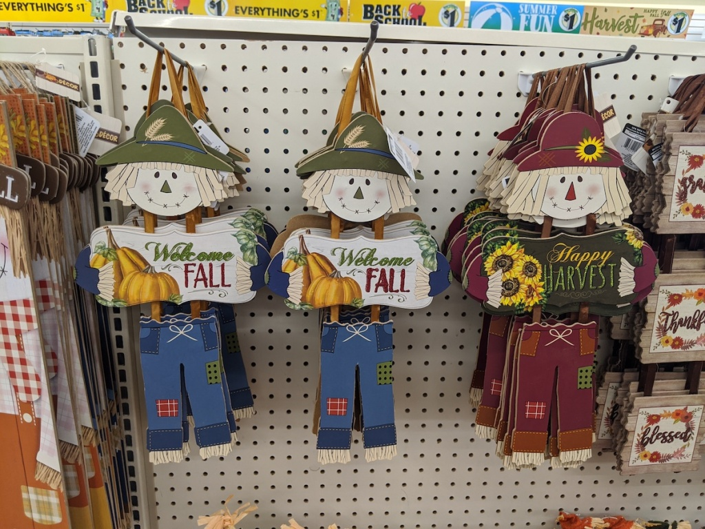 three Dangling Scarecrow Welcome Signs hanging at dollar tree