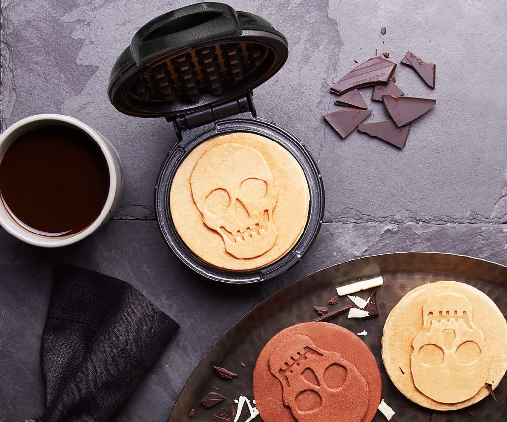 mini skull waffle maker on table with cup of coffee and plate of skull waffles