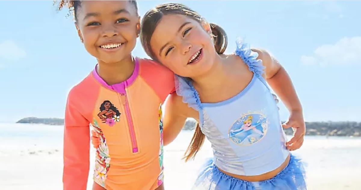 two girls wearing disney swimwear at the beach