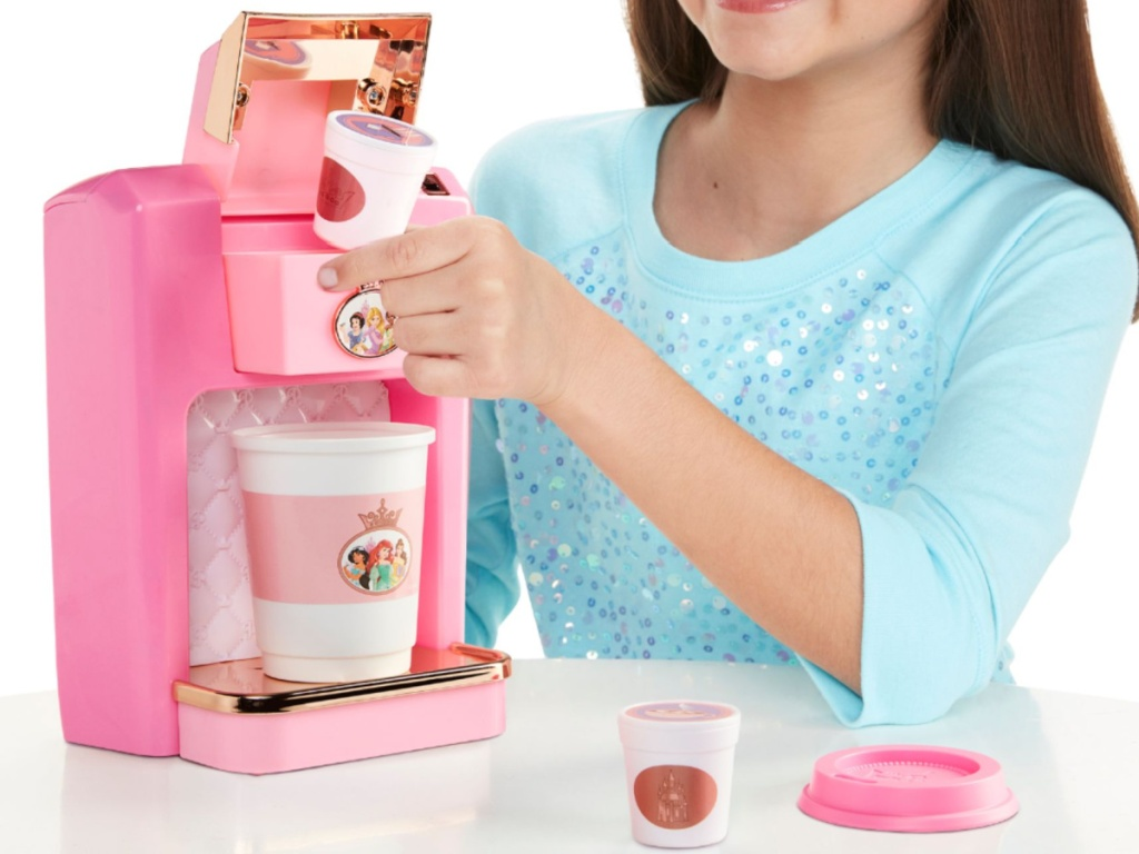 girl playing with pink toy coffee maker