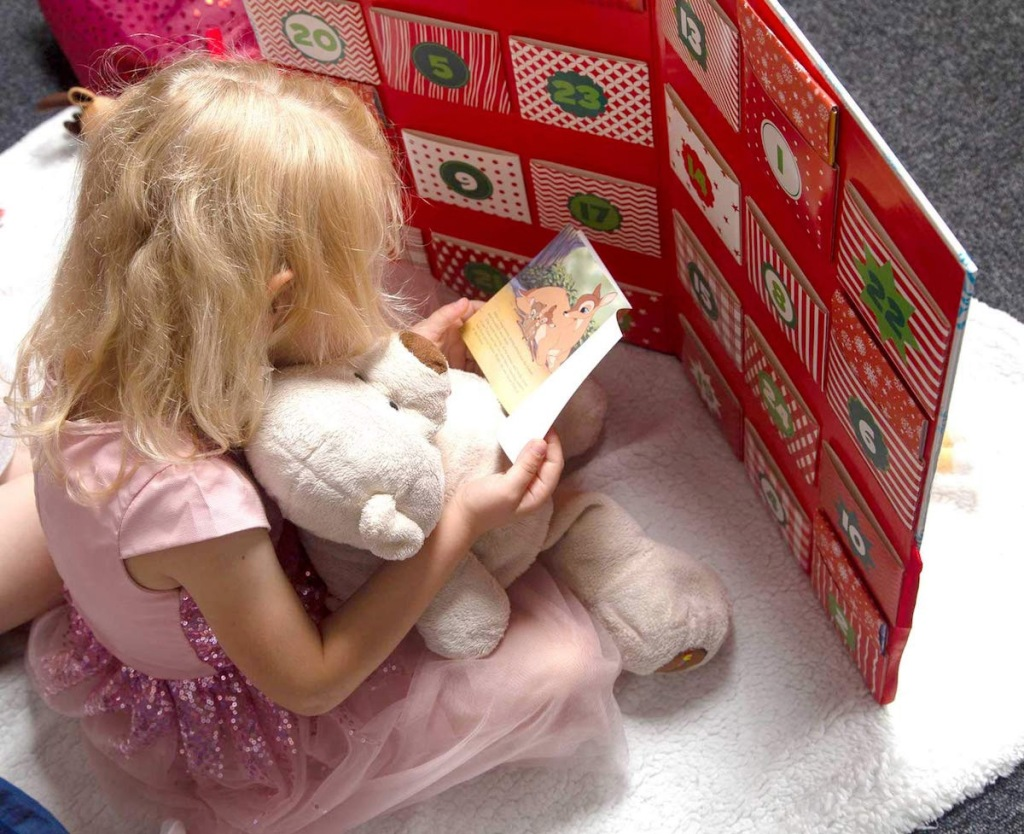 girl sitting on floor holding stuffed animal and disney book in front of large disney christmas story advent calendar