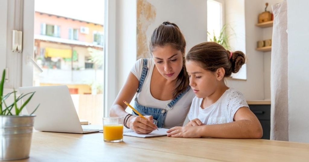 A mom helping daughter with homework at a kitchen table