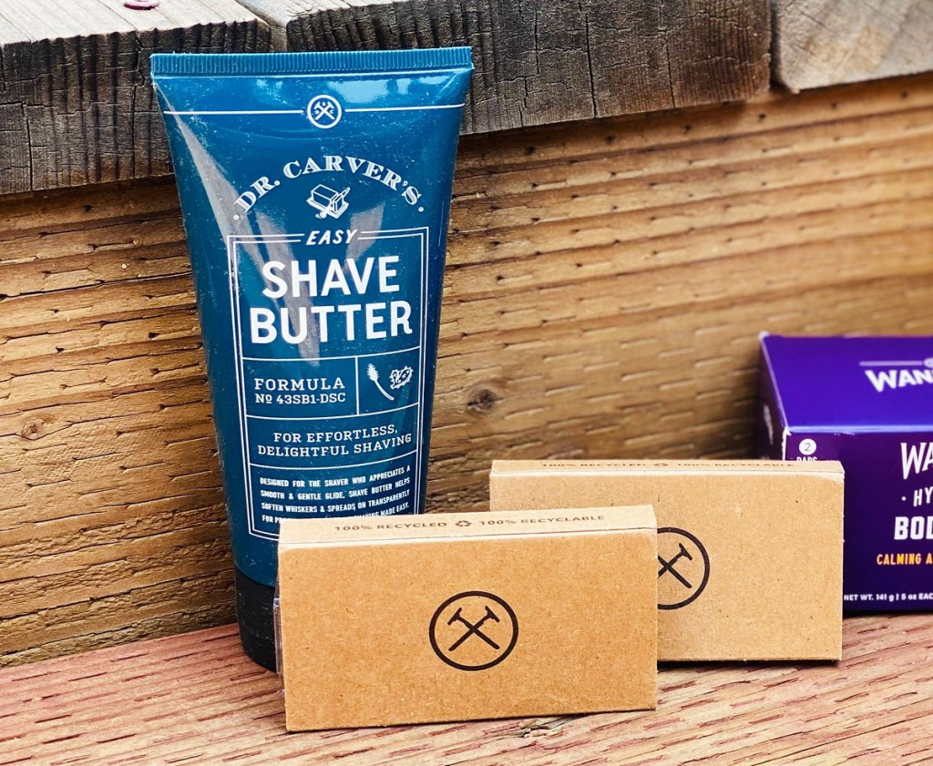 blue bottle of shave butter in front of two razor refill boxes on wood deck