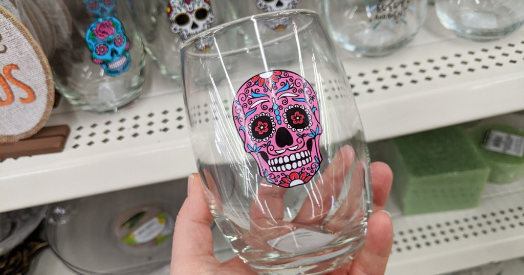 person holding a stemless wine glass with a pink sugar skull printed on it