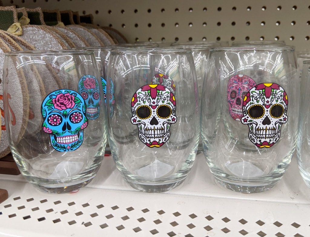 stemless wine glasses with white and blue sugar skulls printed on them on white store shelf