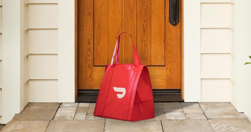 red food delivery service bag in front of home's front door