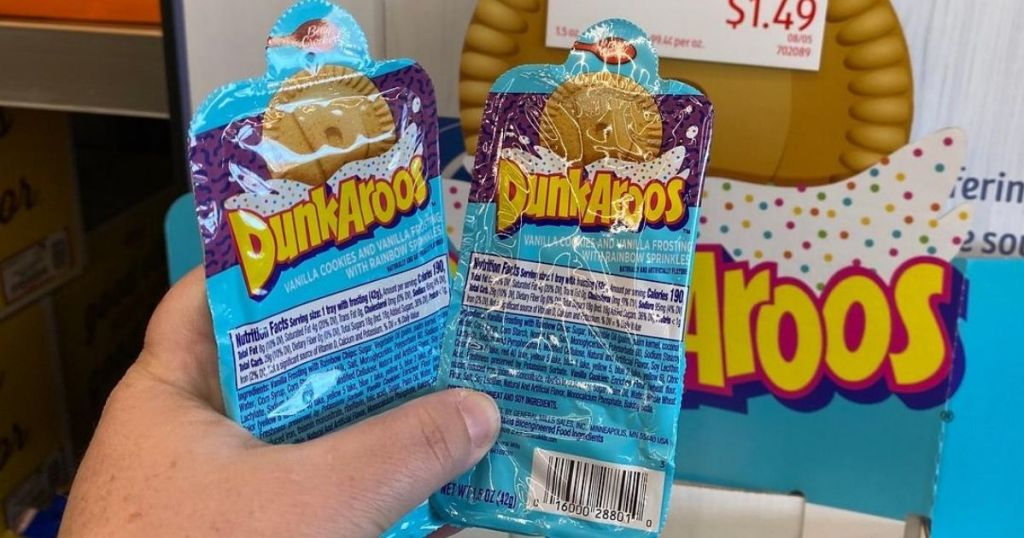 Hand holding two packs of Dunkaroos dippable cookie snacks