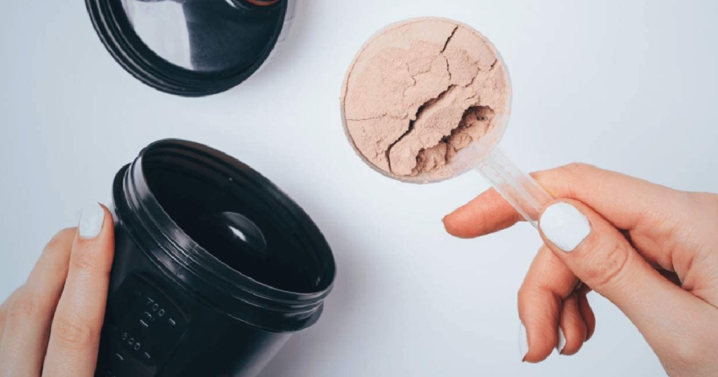 woman's hand holding a scoop of chocolate protein powder and a blender type bottle