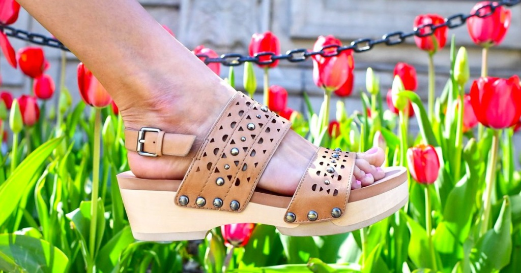 woman wearing a pair of brown leather platform sandals with red tulips blooming in background