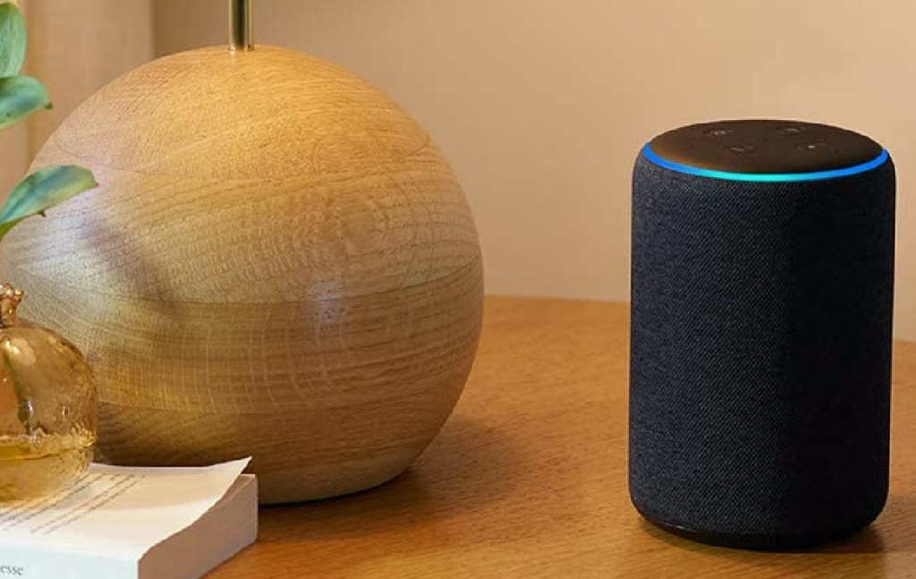 black smart speaker on table with lamp and book