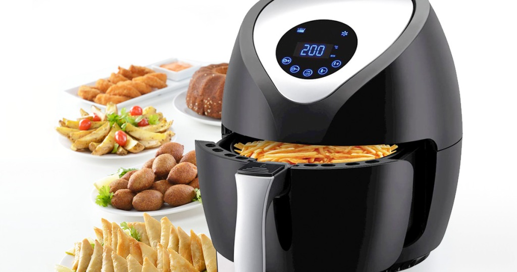 black air fryer with digital display with basket open with fries inside and plates of fried foods around it