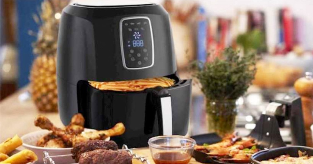 Best Air Fryer - black air fryer with basket open showing french fires inside, sitting on kitchen counter surrounded by other fried foods