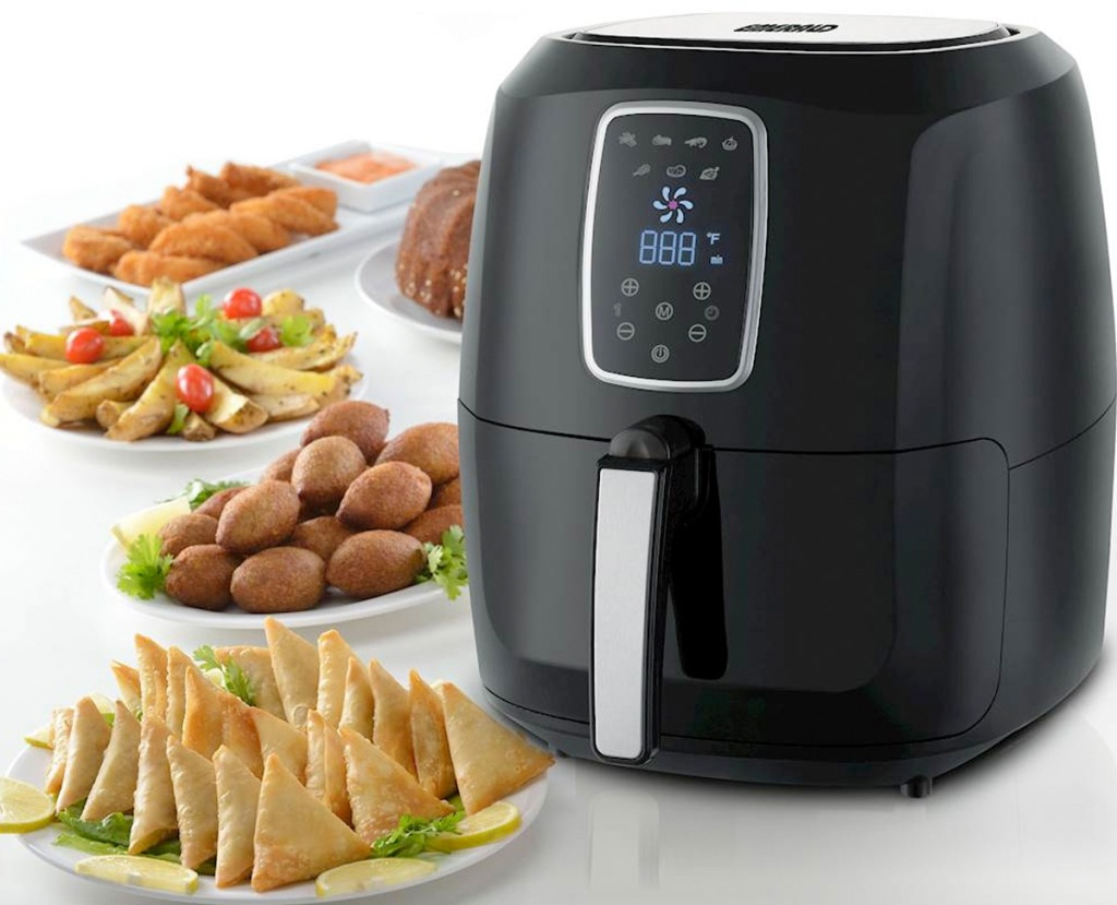 Best Air Fryer - black air fryer with digital controls sitting on counter with plates of fried foods next to it