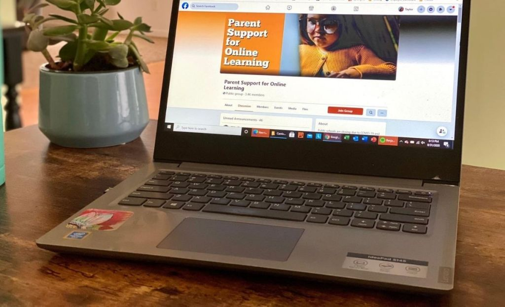 A laptop on a desk with a facebook page open