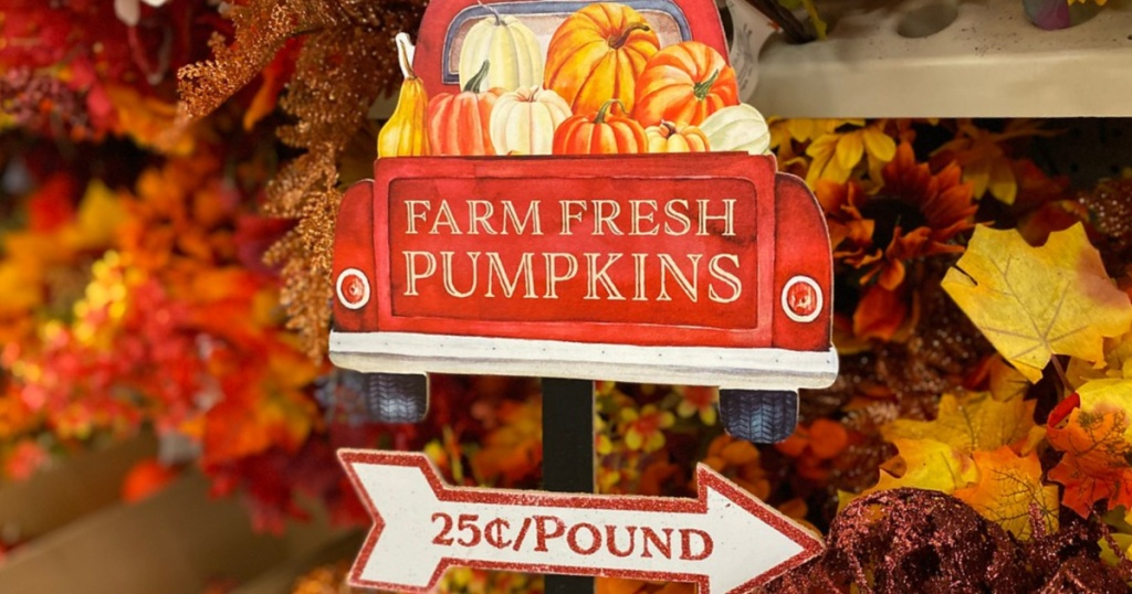 red truck pumpkin lawn sign and foliage decor in store