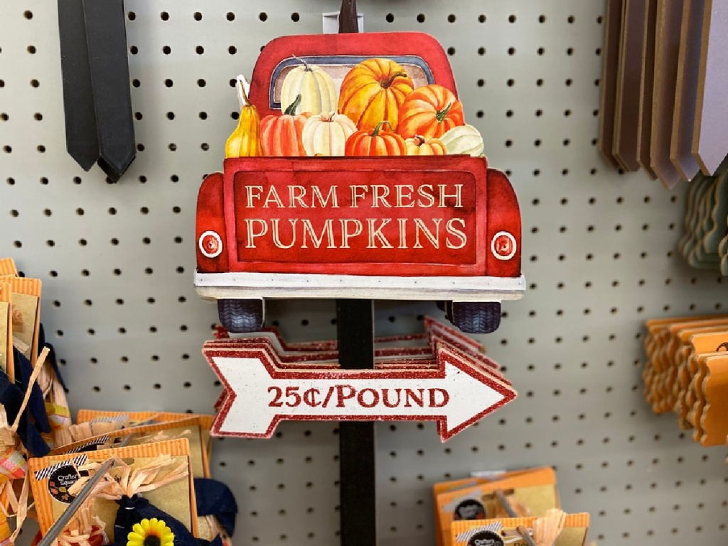 red truck pumpkin lawn sign hanging in store