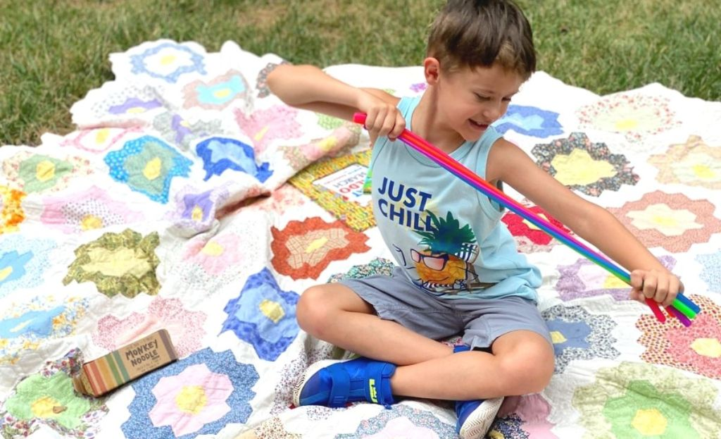 A boy playing with a stretchy fidget toy on a blanket outside
