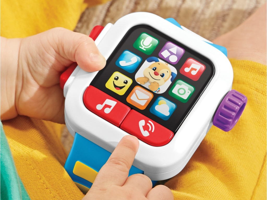 kid holding Fisher-Price Laugh & Learn Time to Learn Smartwatch